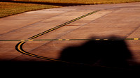 Edinburgh Airport, airside, taxiway Alpha, the shadow of an Airside Ops vehicle stretches over ground markings, 21 June 2010