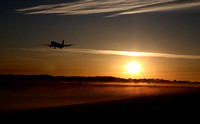 Edinburgh Airport, airside, aircraft landing on runway 24 with low sun behind and fog on the ground, 21 June 2010