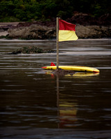 Flagged, red and yellow beach flag with matching surfboard