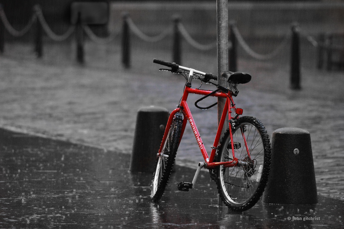 Red bike outside in the rain on Edinburgh's Royal Mile