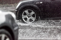 car drivers through surface water on road